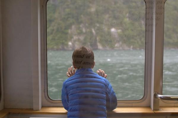 child looking out of boat window