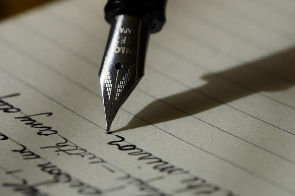 Image of someone writing with a fountain pen
