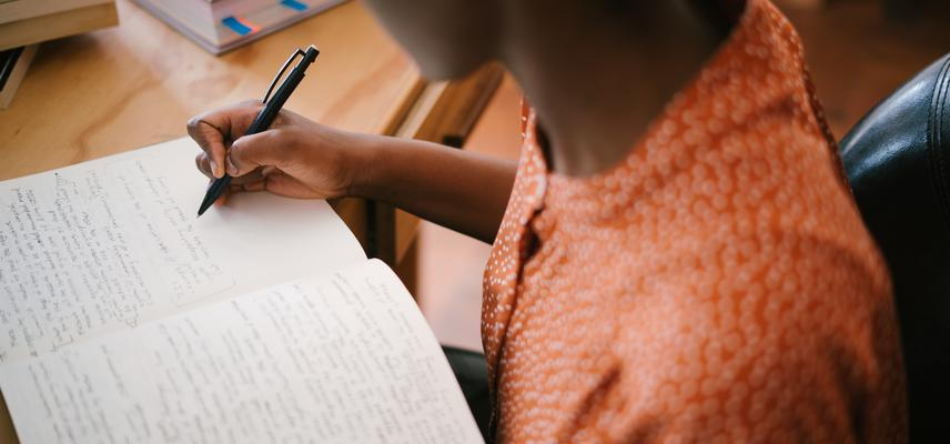 Photo of woman writing on notebook