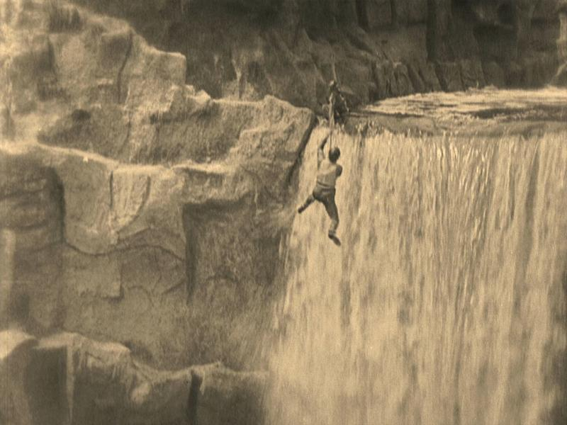 A black and white film still of Buster Keaton dangling from a rope in front of a waterfall
