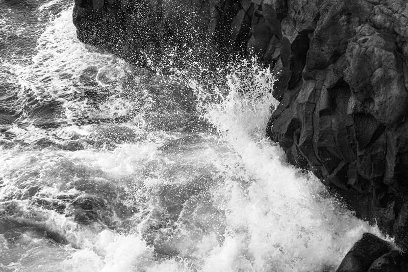 A black and white image of waves crashing on rocks