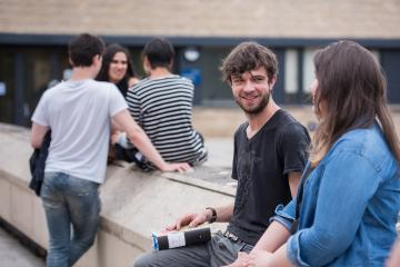 Students outside sitting on wall and chatting