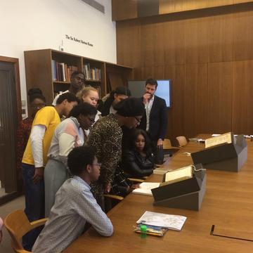Group of students at the Weston Library looking at books on a table