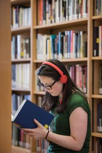 Student wearing orange headphones reading a book in a library
